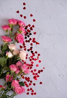Composition florale avec des roses roses et des coeurs de confettis rouges sur fond gris. contexte de la saint-valentin. mise à plat, vue de dessus.