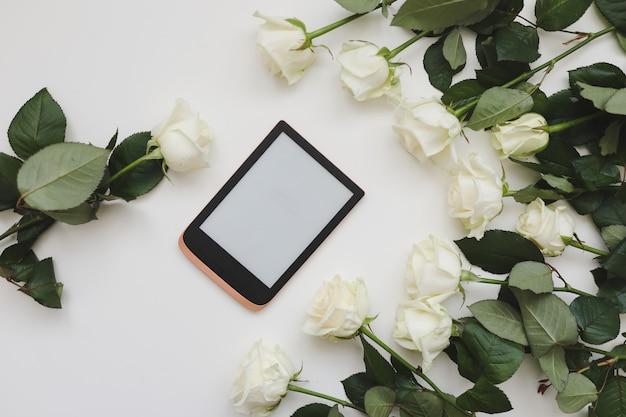 Composition florale avec tablette roses blanches fraîches sur table blanche, mise à plat, vue du dessus