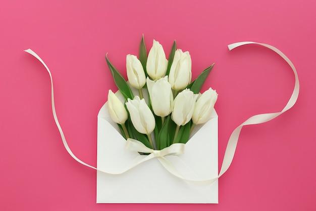 Composition florale de tulipes blanches dans une enveloppe sur rose corail
