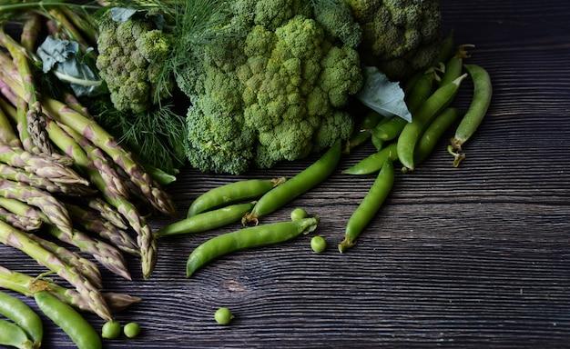Composition sur fond de bois foncé de produits végétariens bio verts: pois, aneth, brocoli, asperges.