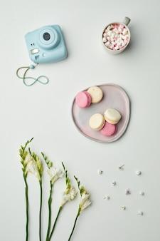 Composition de fond minimale de l'appareil photo instantané sur tout fond de table avec des accents floraux et tasse de cacao sucré,
