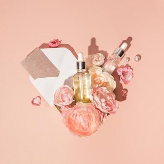 Composition en forme de coeur de cosmétiques naturels, sérums de soins de la peau combinés avec des fleurs et carte-cadeau, fond pastel de pêche