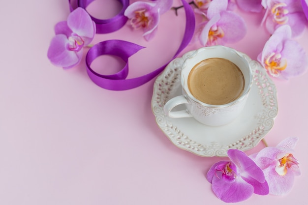 Composition de frais généraux de fleur sur la vue de dessus de surface rose clair. tasse de café et fleurs d'orchidées perple. concept d'humeur de café