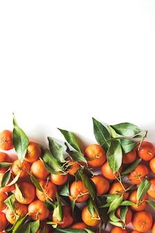 Composition de fruits oranges avec feuilles vertes et tranche sur fond de bois blanc, vue du dessus