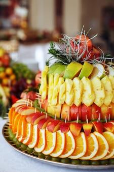 Composition de fruits avec des pommes, des ananas, des raisins.
