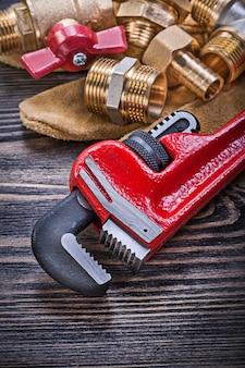 Composition de gants de sécurité en cuir et équipement de plomberie en laiton sur planche de bois
