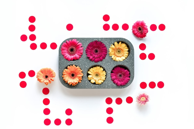 Composition géométrique, fleurs de gerbera vibrantes et cercles de papier ronds autour de la forme de cuisson rectangle.