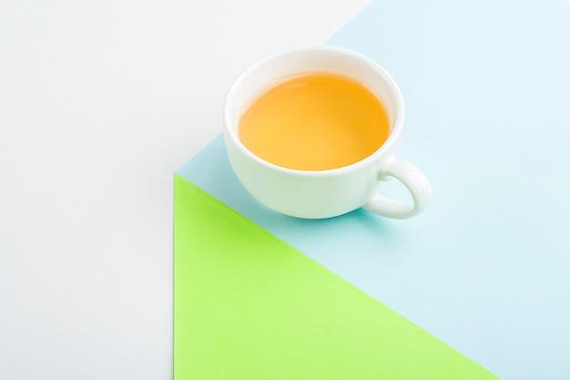 Composition géométrique minimaliste avec tasse de thé vert asiatique sur bleu et vert