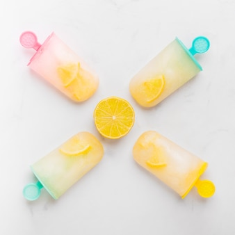 Composition de glace au citron et à la glace avec agrumes sur des bâtons colorés