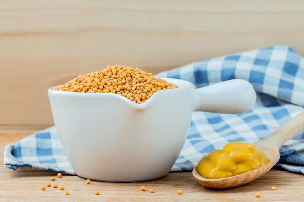 Composition de graines de moutarde et de moutarde sur fond de bois.