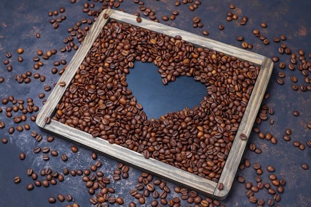 Composition avec des grains de café torréfiés et des biscuits en forme de grain de café sur une surface brun foncé