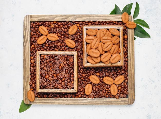 Composition avec des grains de café torréfiés et des biscuits en forme de grain de café sur une surface claire