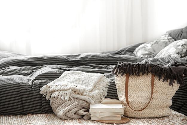 Composition avec grand sac en paille en osier, couvertures et livres sur fond de chambre.