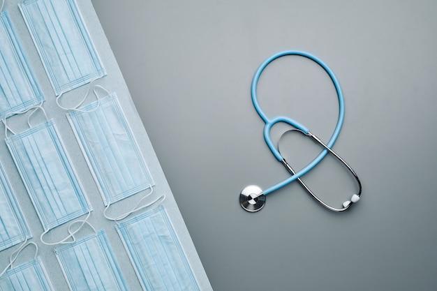 Composition graphique de haut en bas de masques médicaux avec stéthoscope disposés sur fond gris,