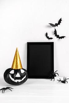 Composition d'halloween. cadre photo noir et village abandonné d'art papier, citrouille sur blanc.