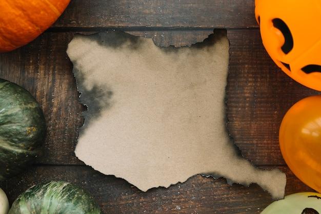 Composition d'halloween avec des citrouilles et du papier brûlé