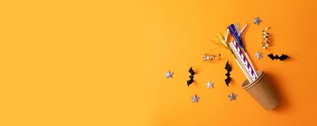 Composition de halloween de verres en papier, tubes multicolores pour boissons, chauves-souris en papier noir, étoiles