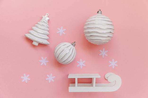Composition d'hiver tout simplement minimaliste objets ornement boule sapin traîneau isolé sur pastel rose
