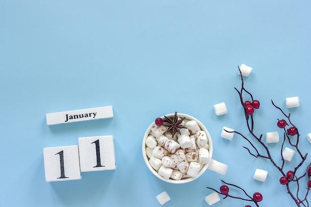 Composition hivernale. cubes de calendrier en bois blanc. données le 11 janvier. tasse de cacao, guimauves et branche décorative avec des baies rouges sur fond bleu vue de dessus mise à plat espace de copie