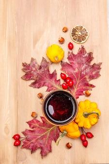 Composition d'humeur confortable d'automne. thé chaud en verre céramique, feuilles d'automne, citrouilles, bruyère, noisettes