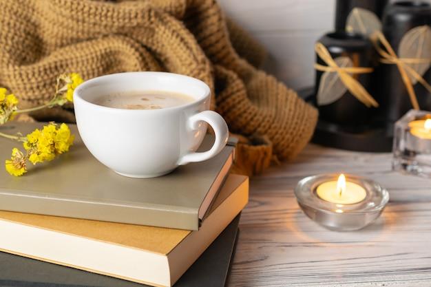 Composition hygge avec café, bougies, livres et plaid tricoté