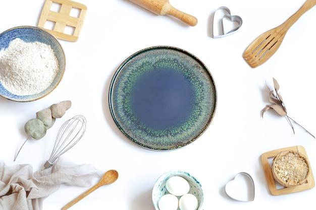 Composition avec des ingrédients de cuisson et des accessoires de cuisine sur une vue de dessus de table blanche.