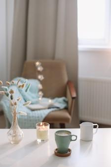 Composition intérieure confortable avec une tasse de café, une bougie et un vase avec des fleurs sur une table basse