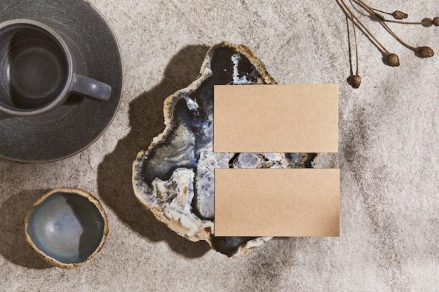 Composition intérieure créative à plat avec des cartes de visite simulées, des roches, des matériaux naturels, des plantes sèches et des accessoires personnels. couleurs neutres, vue de dessus, modèle.