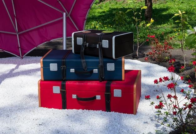 Composition de jardin décoratif de trois valises colorées les unes sur les autres sur du gravier blanc dans le jardin