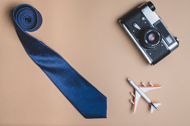 La composition de jour de père avec cravate, avion et appareil photo
