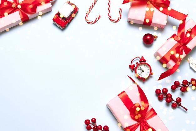 Composition de joyeux noël et joyeuses fêtes avec des cadeaux de noël, décor rouge, jouet de voiture, canne en bonbon et paillettes