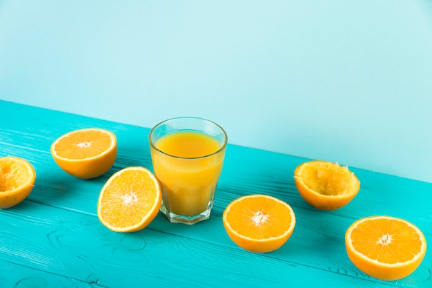 Composition de jus d'orange frais sur une table bleue