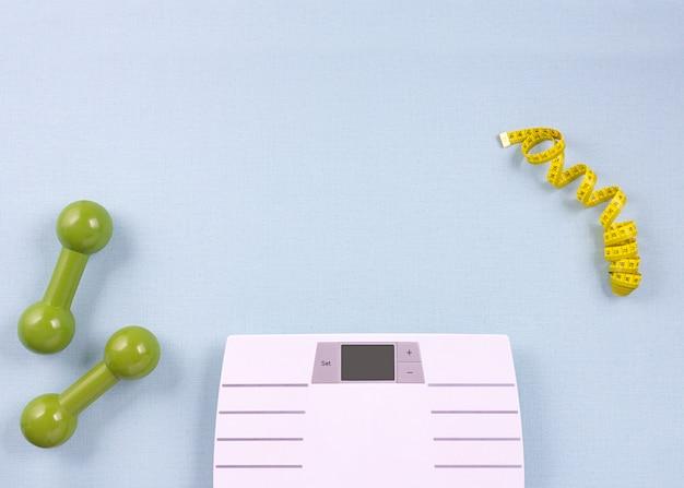 Composition laïque à plat avec des articles de sport, échelles sur fond bleu. concept de perte de poids. vue de dessus, espace de copie.