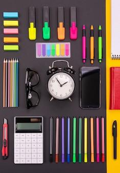 Composition laïque plate de bureau d'affaires avec smartphone, calculatrice, autocollants et stylos sur fond noir et jaune coloré