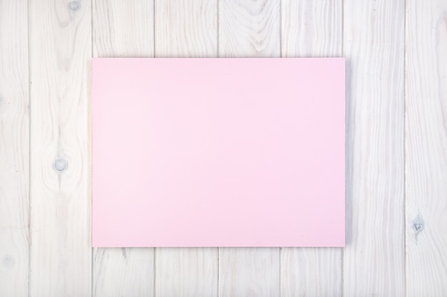 Composition laïque plate avec un tableau rose sur une table en bois blanche