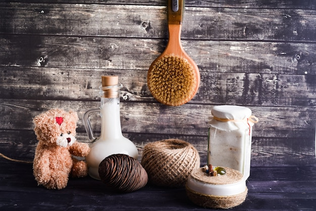 La composition laïque avec des produits de soins corporels. un pot de crème naturelle, une bouteille d'huile de coco, une pièce de pin et un ours en peluche