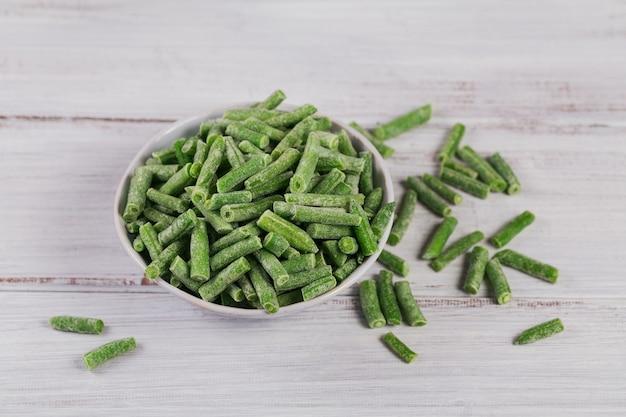 Composition avec des légumes surgelés biologiques sur un fond en bois blanc. haricots verts dans un bol