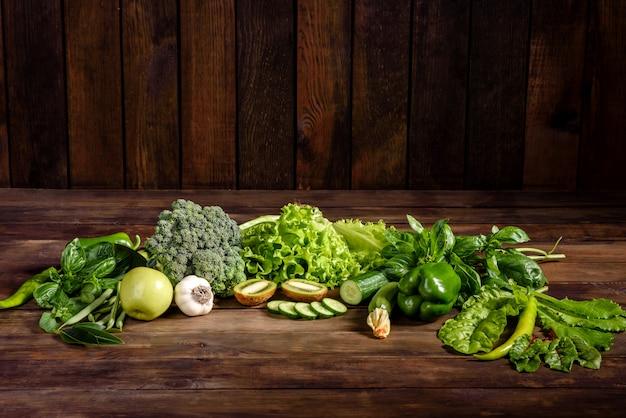 Composition de légumes verts brillants et juteux près d'épices et d'herbes