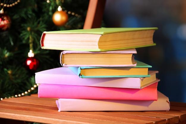 Composition avec des livres sur chaise sur fond d'arbre de noël