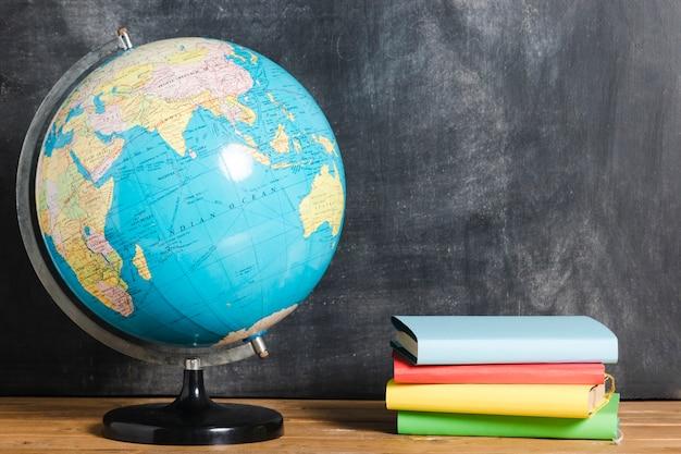 Composition de livres colorés et globe