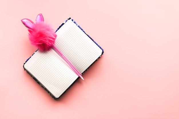 Composition lumineuse d'accessoires de mode. bloc-notes à paillettes scintillantes et stylo décoré amusant. fournitures de papeterie sur fond pastel doux. mise à plat, vue de dessus