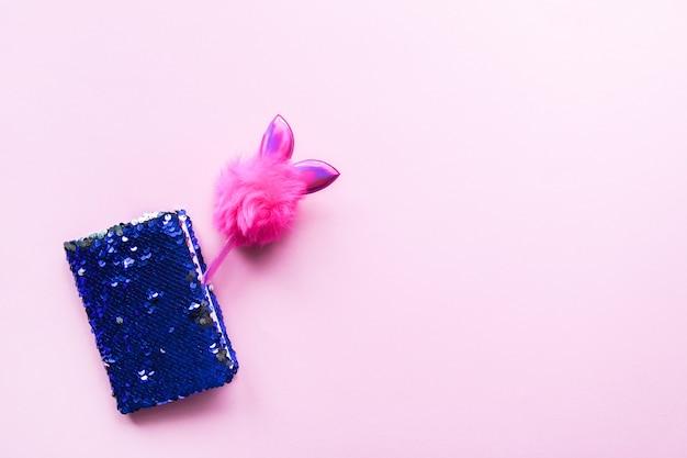 Composition lumineuse d'accessoires de mode. bloc-notes à paillettes scintillantes et stylo décoré amusant. objets sur fond pastel doux. mise à plat, vue de dessus.