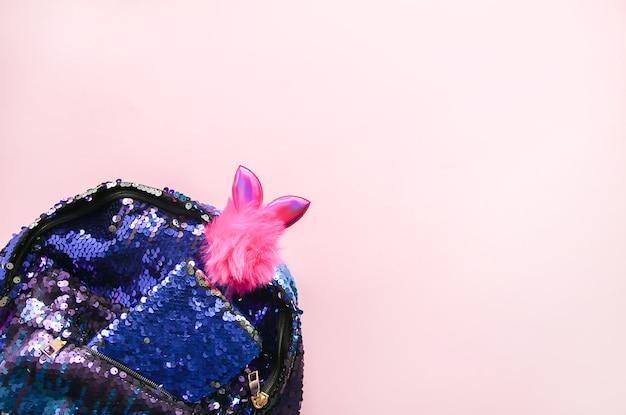 Composition lumineuse d'accessoires de mode. sac à dos à paillettes scintillantes, bloc-notes et stylo décoré rigolo. différents objets sur fond pastel doux. mise à plat, vue de dessus.