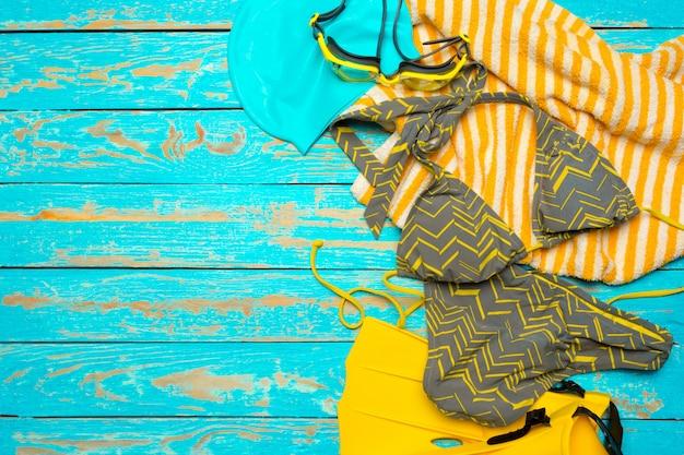 Composition avec maillot de bain sur bois de couleur