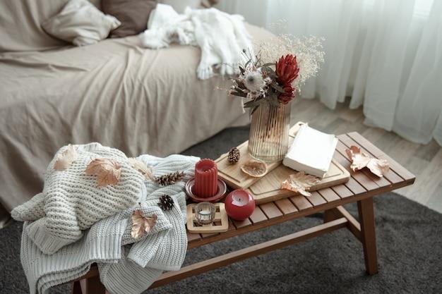 Une composition de maison confortable avec des bougies et un livre de pulls en tricot
