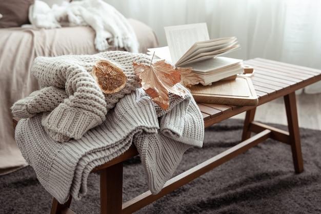 Une composition de maison confortable avec un pull en tricot, un livre et des feuilles à l'intérieur de la pièce.