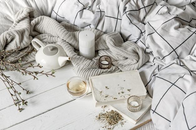 Composition maison confortable avec une tasse de tisane et des livres sur une surface en bois.