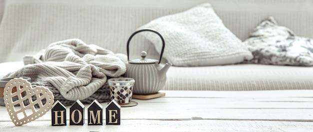 Composition de maison confortable avec une théière, des articles tricotés et des détails de décoration scandinave. concept de confort de la maison et de style moderne.