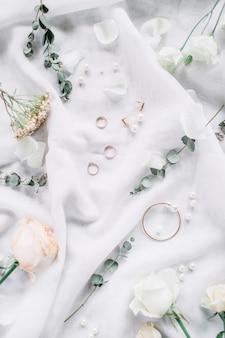 Composition de mariage avec des branches d'eucalyptus, anneaux de mariée, fleur rose sur textile blanc