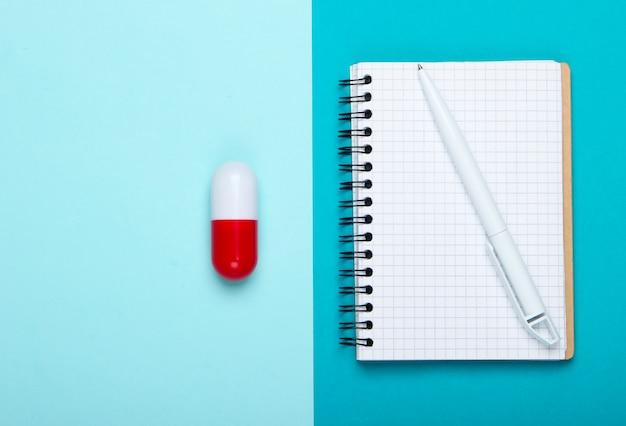 Composition de médecine plate laïque. capsule de pilule, cahier sur fond bleu pastel. vue de dessus